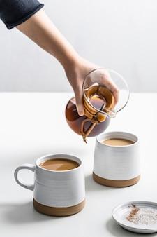 テーブルの上のマグカップにコーヒーを注ぐ高角度の手