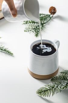コーヒーマグにクリームを注ぐ高角度の手