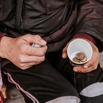 Высокий угол бездомного с чашкой и монетами