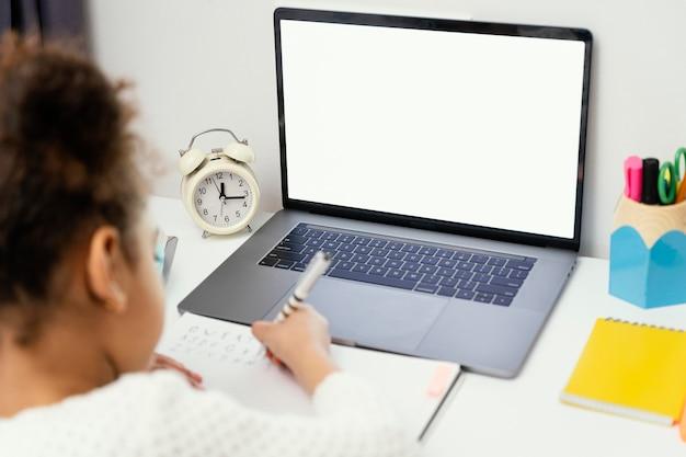 ノートパソコンでオンライン学校中に自宅で小さな女の子の高角度