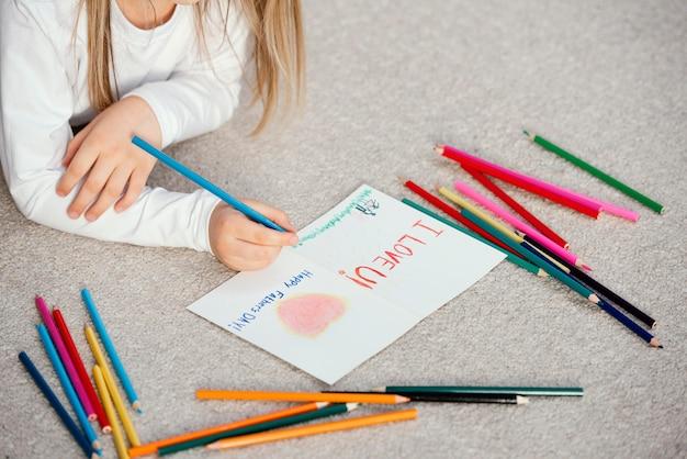 Высокий угол маленькой девочки, держащей чертежную карточку на день отца