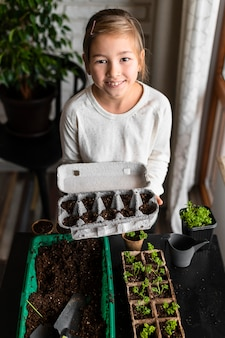 어린 소녀가 달걀 카톤에 심은 씨앗을 들고 높은 각도