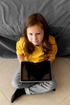 Высокий угол маленькой девочки с помощью планшета