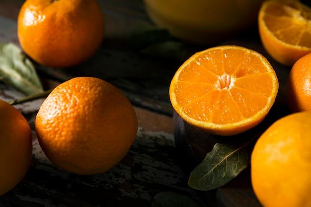 Высокий угол большого количества осенних апельсинов с листьями