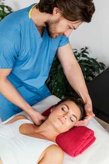여성 환자의 목 척추를 검사하는 남성 정골 치료사의 높은 각도