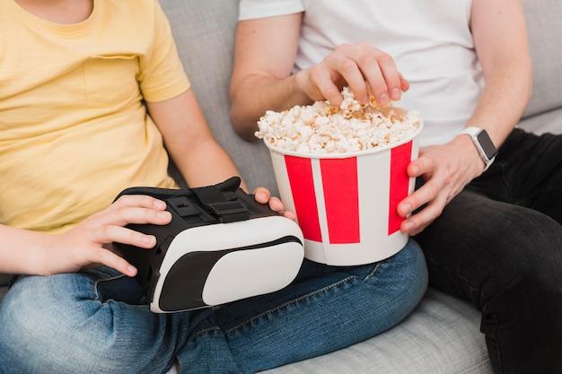 Высокий угол человека и мальчика, проведение виртуальной реальности гарнитуры и попкорна