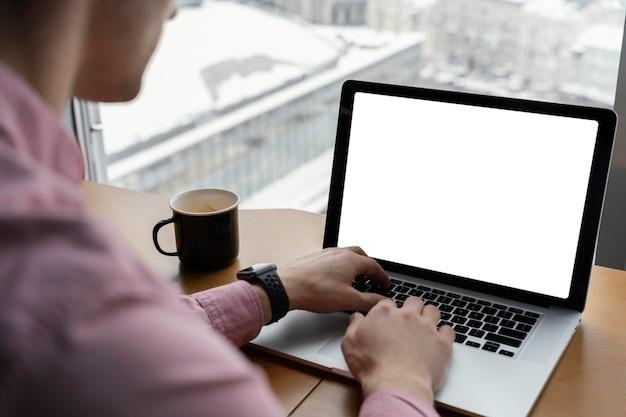 Высокий угол человека, работающего в офисе с ноутбуком