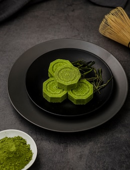 Высокий угол чая маття на тарелку с травами