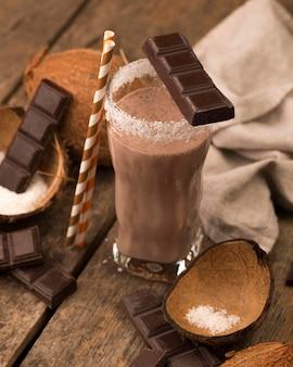 Стакан для молочного коктейля под высоким углом на подносе с шоколадно-кокосовой стружкой