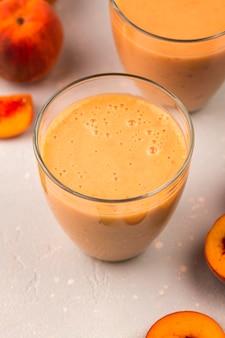 Высокий угол бокалов для молочного коктейля с персиками