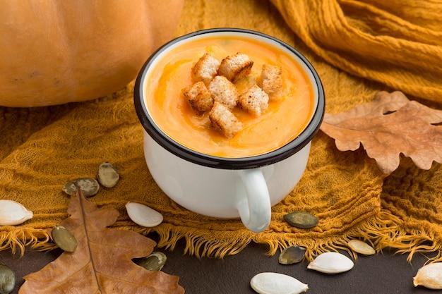 Кружка под высоким углом с зимним супом из кабачков с гренками