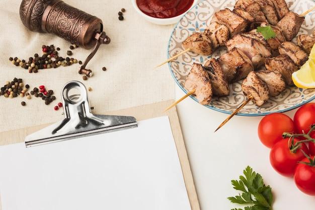 Высокий угол наклона блокнота с тарелкой вкусного кебаба и мельницей для приправ