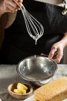 Шеф-кондитер под большим углом использует венчик для ингредиентов торта
