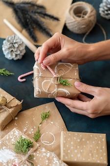 Высокий угол лица, украшающего рождественский подарок конфетой