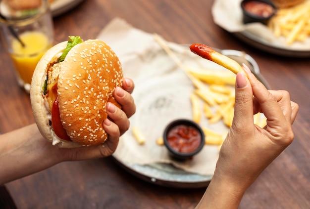 ハンバーガーとフライドポテトを食べる人の高角度