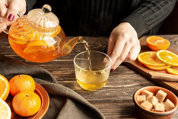 Высокий угол лица наливая чай концепции