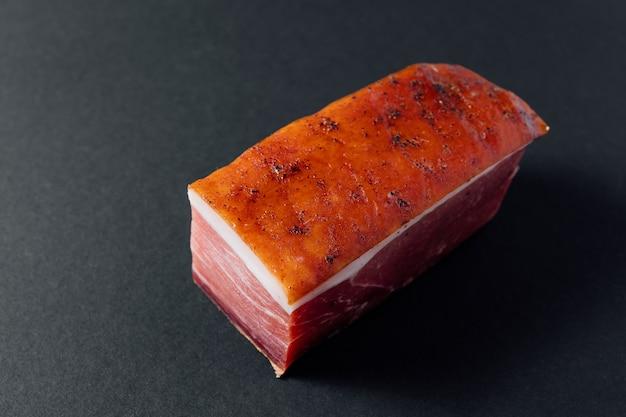 얇은 층의 라드와 훈제 건조 크러스트와 향신료를 곁들인 돼지고기 고기 조각의 높은 각도...