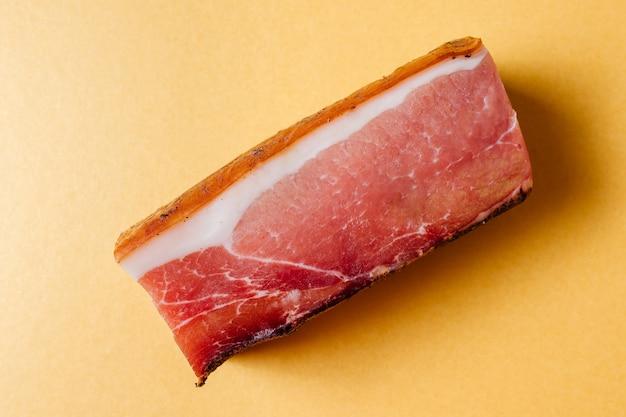얇은 층의 라드와 노란색에 향신료를 곁들인 훈제 건조 크러스트를 곁들인 돼지 고기 조각의 높은 각도 ...