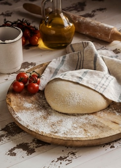 Тесто для пиццы под высоким углом, покрытое тканью и помидорами