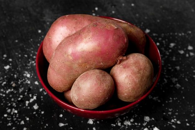 Высокий угол картофеля в миске с солью