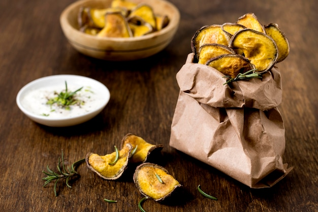 Высокий угол жареного картофеля в бумажном пакете с соусом