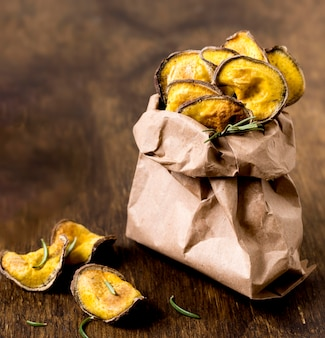 Высокий угол жареного картофеля в бумажном пакете