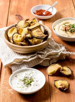 Высокий угол жареного картофеля с соусом и хумусом