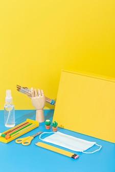Высокий угол школьных принадлежностей с маской и карандашами