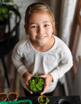 집에서 냄비에 식물을 들고 웃는 어린 소녀의 높은 각도