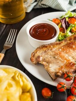 Высокий угол стейка на тарелке с чипсами и пивом