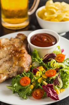 Высокий угол стейка на тарелке с салатом и пивом