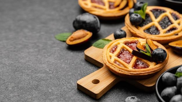 Высокий угол сладких пирогов с фруктами и копией пространства