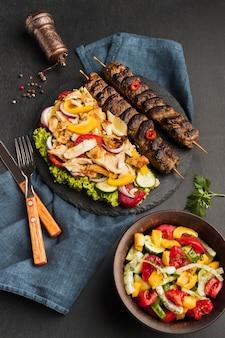 Высокий угол наклона вкусного шашлыка на грифеле с другими блюдами и столовыми приборами