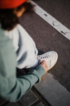 Подросток завязывает шнурки на открытом воздухе под высоким углом