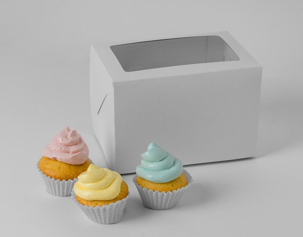 Высокий угол трех кексов с упаковочной коробкой