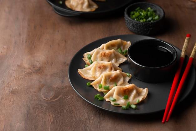Высокий угол традиционного азиатского блюда с палочками для еды и зеленью