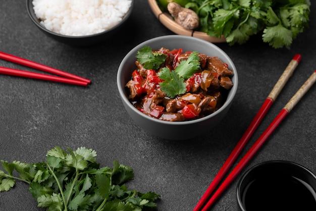 Высокий угол традиционного азиатского блюда с палочками для еды и рисом