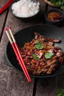 Высокий угол традиционного азиатского блюда с мясом и палочками для еды