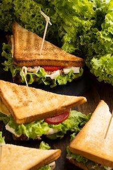 Высокий угол треугольного салата и бутербродов с помидорами