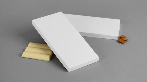 Высокий угол плитки белого шоколада с орехами и упаковкой