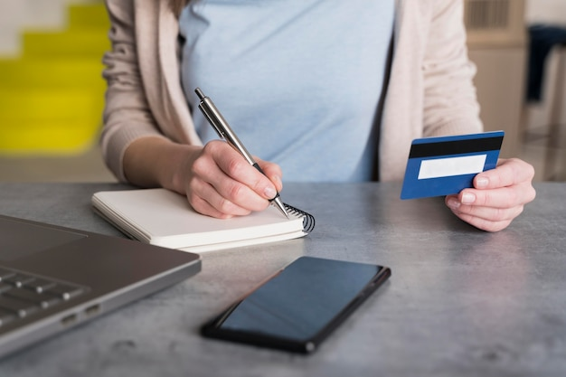 Высокий угол женщины дома холдинг кредитной карты и и писать в блокноте