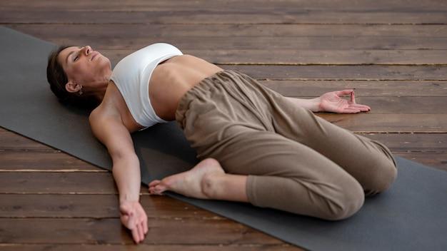 Высокий угол женщины, практикующей йогу дома