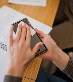 Высокий угол женщины дезинфицирует свой телефон перед уроком