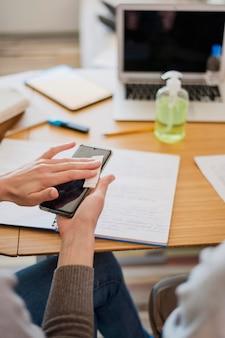 Высокий угол женщины дезинфицирует свой смартфон перед уроком