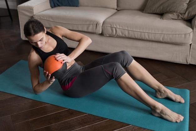 Высокий угол женщины, осуществляющие с мячом на коврик для йоги