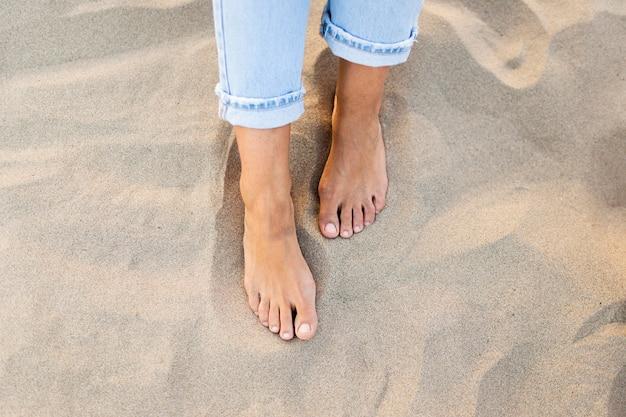 해변에서 모래에 여자 피트의 높은 각도