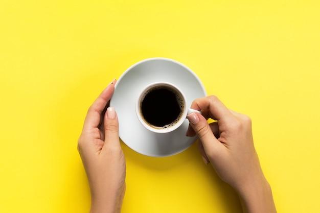 노란색 배경에 커피 컵을 들고 있는 여성의 높은 각도 미니멀리즘 스타일입니다. 평면 위치, 상위 뷰가 격리되었습니다.