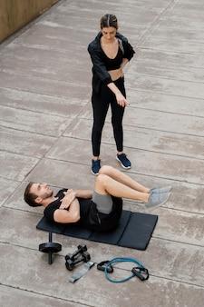 야외에서 남자 훈련을 돕는 여자의 높은 각도