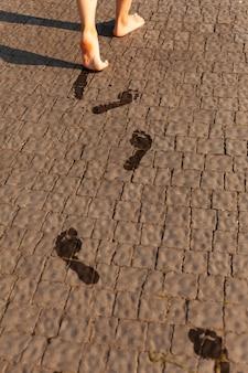 歩きながら地面に濡れた足音を残す女性の高角度