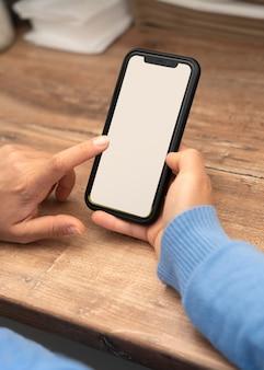 スマートフォンでテイクアウト食品を注文する女性の高角度